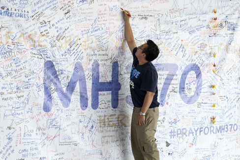 A man writes a message on a banner for missing Malaysian Airline System Bhd. Flight 370 at Kuala Lumpur International Airport (KLIA) in Sepang, on Friday, March 14, 2014