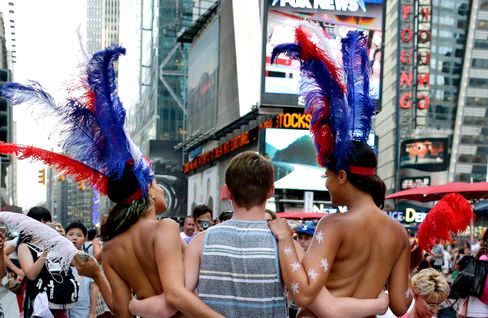 In this photo taken on Tuesday, July 28, 2015, a tourist poses for a photo with two women clad in thongs and body paint in Times Square, in New York.