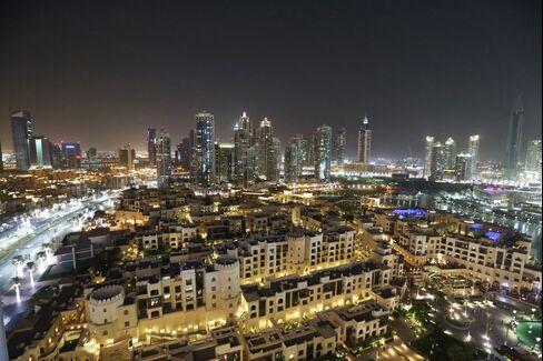 The city skyline sits illuminated at night in downtown Dubai, United Arab Emirates.