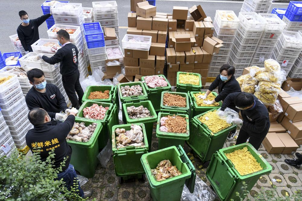 Employees of a catering company throw out expired food in Changsha, March 2020.