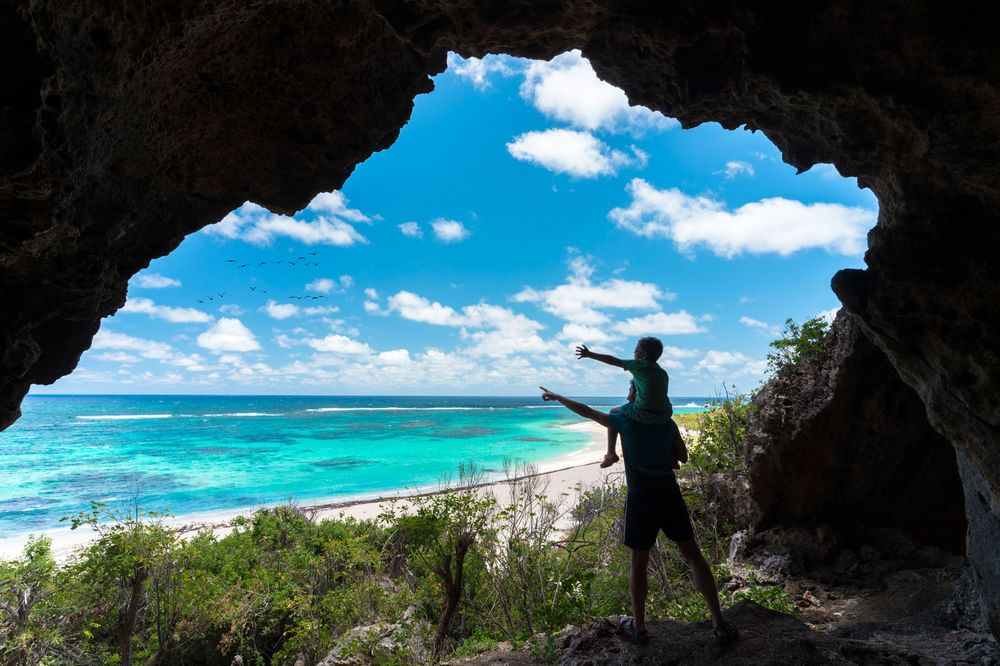 Father and child in sea cave, Two Foot Bay, Barbuda, Caribbean