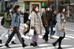 Pedestrians wearing protective masks cross an road in the Ginza area in Tokyo, Japan.
