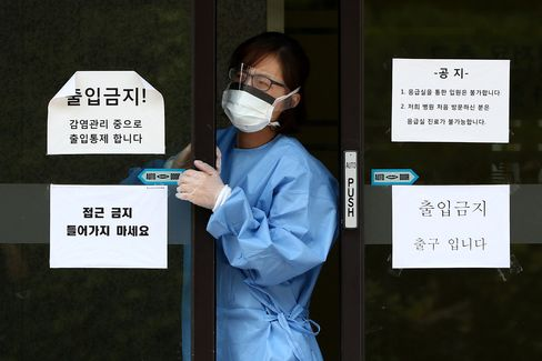 A medical staff employee wearing a mask exits a closed hospital emergency room and restricted area at the Samsung Medical Center in Seoul, South Korea, on Sunday, June 14, 2015. South Korea reported several cases of Middle East respiratory syndrome as the country is shaken by fears of contagion.