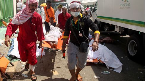 Saudi emergency personnel and Hajj pilgrims carry a wounded person at the site where at least 450 were killed and hundreds wounded in a stampede in Mina, near the holy city of Mecca, at the annual hajj in Saudi Arabia, on Sept. 24, 2015.