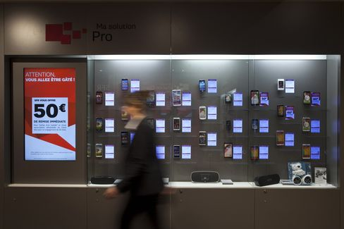 An Employee Passes Mobile Phones in an SFR Store in Paris