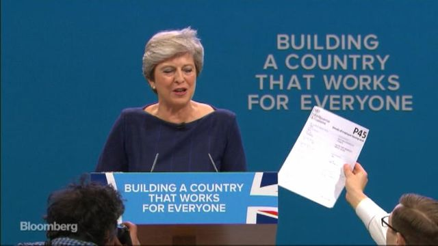 Lee Nelson hands Theresa May a P45 during keynote speech