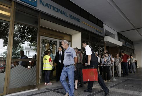 A security guard delivers cash to a bank branch in Athens on July 6