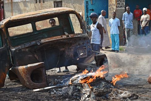 Protestors Stand by a Burning Vehicle in Bujumbura