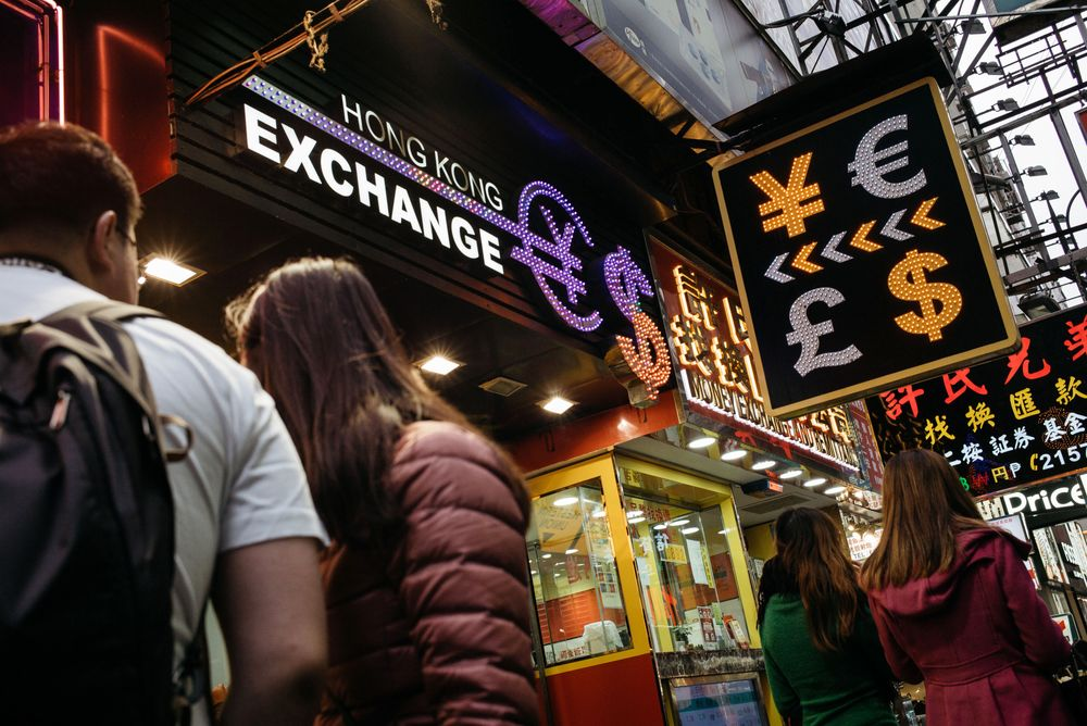 Pedestrians Walk Past A Currency Exchange In Hong Kong