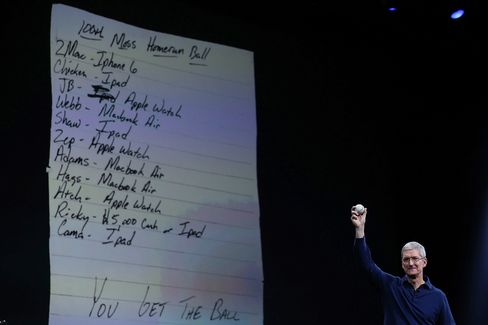 Apple CEO Tim Cook Holds up a baseball as he delivers the keynote address during Apple WWDC on June 8, 2015 in San Francisco, California.