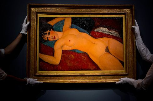 Art handlers hang the painting 'Nu couche' by artist Amedeo Modigliani.