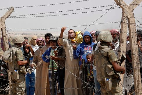 Refugees wait on the Syrian side of the border to cross into Turkey in June.