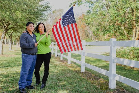 Ish and Rita hold an American flag in the backyard of their South Carolina home.