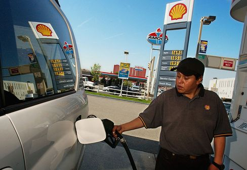A gas station attendant pumps gas into an SUV at a Shell gas station in Jersey City, New Jersey.