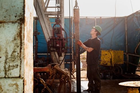A worker checks the drilling rig before attaching it to the turntable on Endeavor Energy Resources LP's Big Dog Drilling Rig 22 in the Permian basin outside of Midland, Texas, U.S., on Friday, Dec. 12, 2014.