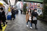 Visitors wearing face masks walk along a sidewalk in Tokyo's Akihabara area, Japan, on Tuesday, Jan. 28, 2020.