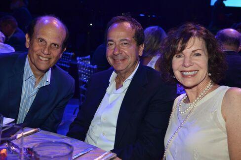 Mike and Lori Milken with John Paulson