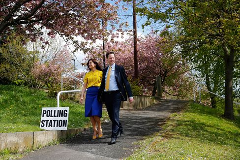 Liberal Democrat Party Leader Nick Clegg, right, and Miriam Gonzalez Durantez, his wife, head to a polling station to cast their votes in the general election in Sheffield, today. Photographer: Paul Thomas/Bloomberg