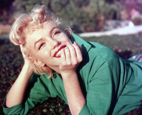 Actress Marilyn Monroe poses for a portrait as she lies on the grass in 1954 in Palm Springs, Calif.