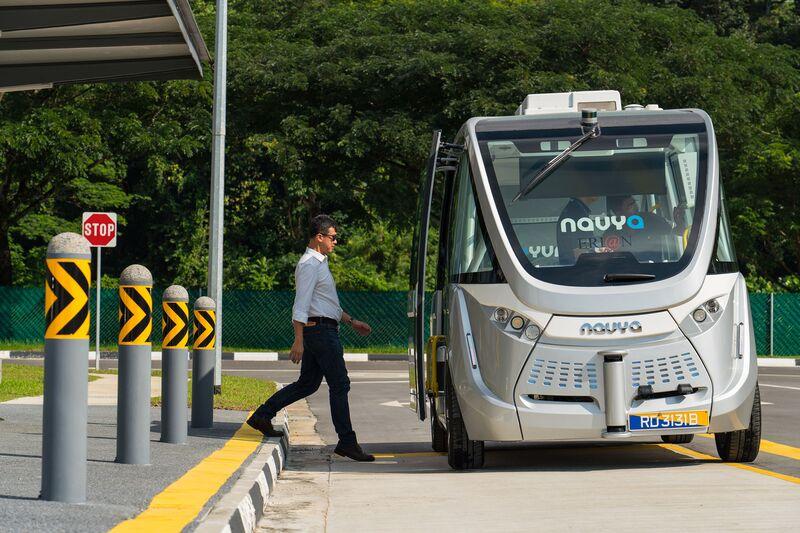 An engineer walks towards a Navya autonomous electric bus. Image: Nicky Loh/Bloomberg