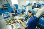 Employees handle toothbrushes on the production line of the Yangzhou Shuguang Toothbrush factory in Yangzhou.