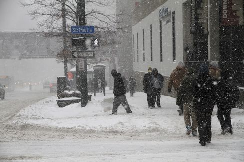 Pedestrians walk along a street during a Snow Storm in Rochester