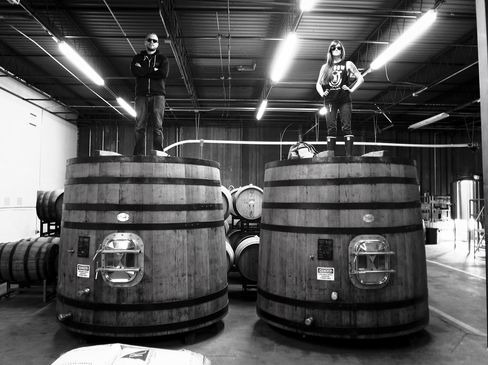 TRVE's Allison Huffman, right, standing atop one of their recently-acquired oak foeders at The Acid Temple.