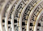 The embossed word Bitcoin sits on the edge of Bitcoins stacked in this arranged photograph in Danbury, U.K., on Thursday, Dec. 10, 2015.