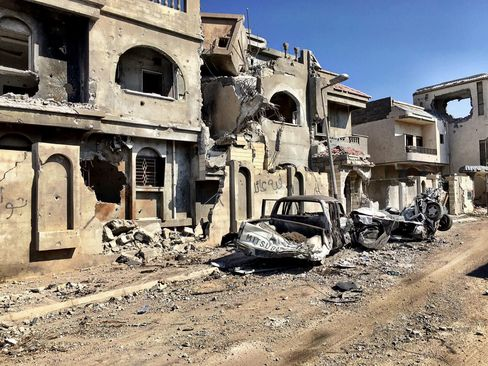 Destroyed buildings and vehicles line a street in Sirte.