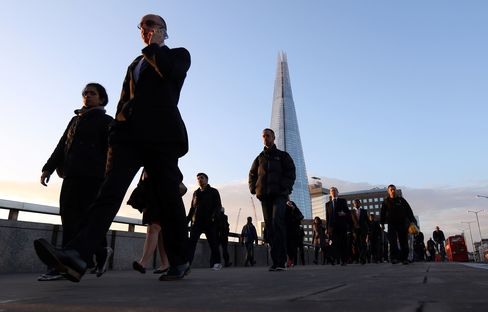 Pedestrians walk across London Bridge towards the City of London financial district, as the Shard tower stands on the horizon in London, on Oct. 10, 2014.