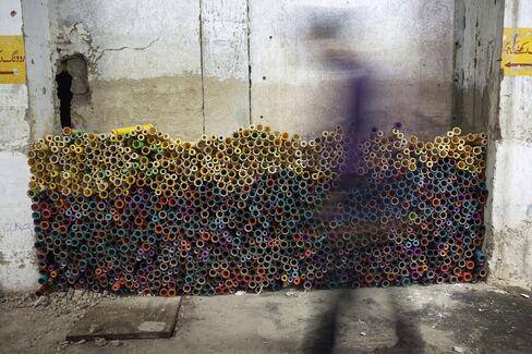 Yarn bobbins sit in a closed textile mill.