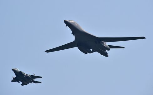 A U.S. B-1B bomber, right, escorted by South Korean F-15K fighter jets over the Osan Air Base