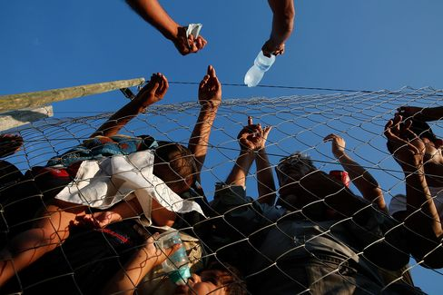 A Macedonian man sells water to migrants held inside a camp shortly after they crossed the Macedonian border from Greece on September 3, 2015 in Gevgelija, Macedonia.