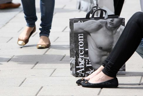 A customer sits with an Abercrombie & Fitch Co. shopping bag in London, U.K.