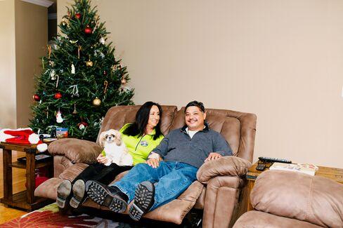 Ish Yniesta sits with his wife, Rita Smith-Yniesta and their shih tzu, Abby.