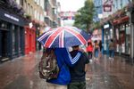 Tourists shelter from the rain under an umbrella featuring an Union flag, also known as a Union Jack, in London, U.K., on Monday, Aug. 13, 2018.