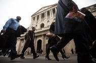 Pedestrians walk past the Bank of England (BOE) in the City of London, U.K..