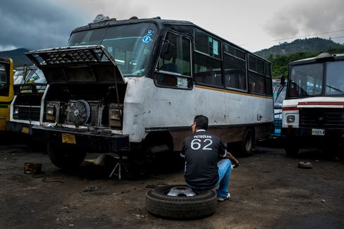 A driver takes a break beside his bus while fixing the brakes on the outskirts of Caracas.