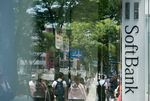 Pedestrians are reflected in the window of a SoftBank Group Corp. store in Tokyo.