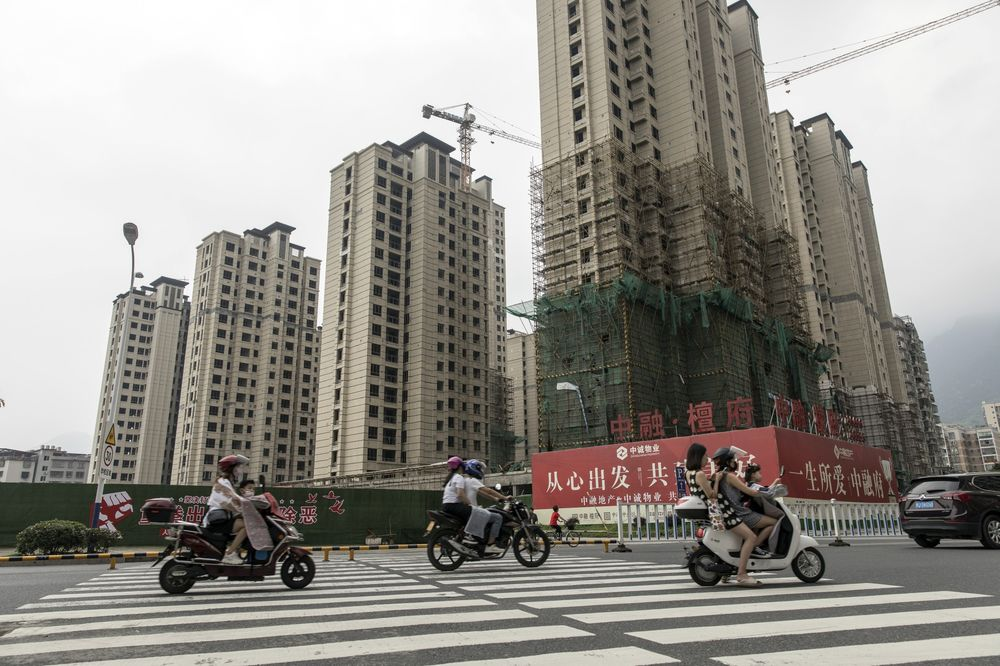 Motorists travel past residential buildings under construction in Ningde, Fujian province, China.