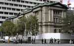 Pedestrians cross a road in front of the Bank of Japan (BOJ) headquarters in Tokyo, Japan.