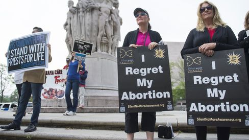 Anti-abortion demonstrators hold signs stating they regret their abortions during a Priests for Life protest outside the US Court of Appeals for the DC Circuit Court as the Court hears the oral arguments in the 'Priests for Life v. US Department of Health and Human Services (HHS)' case in Washington, DC, on May 8, 2014.
