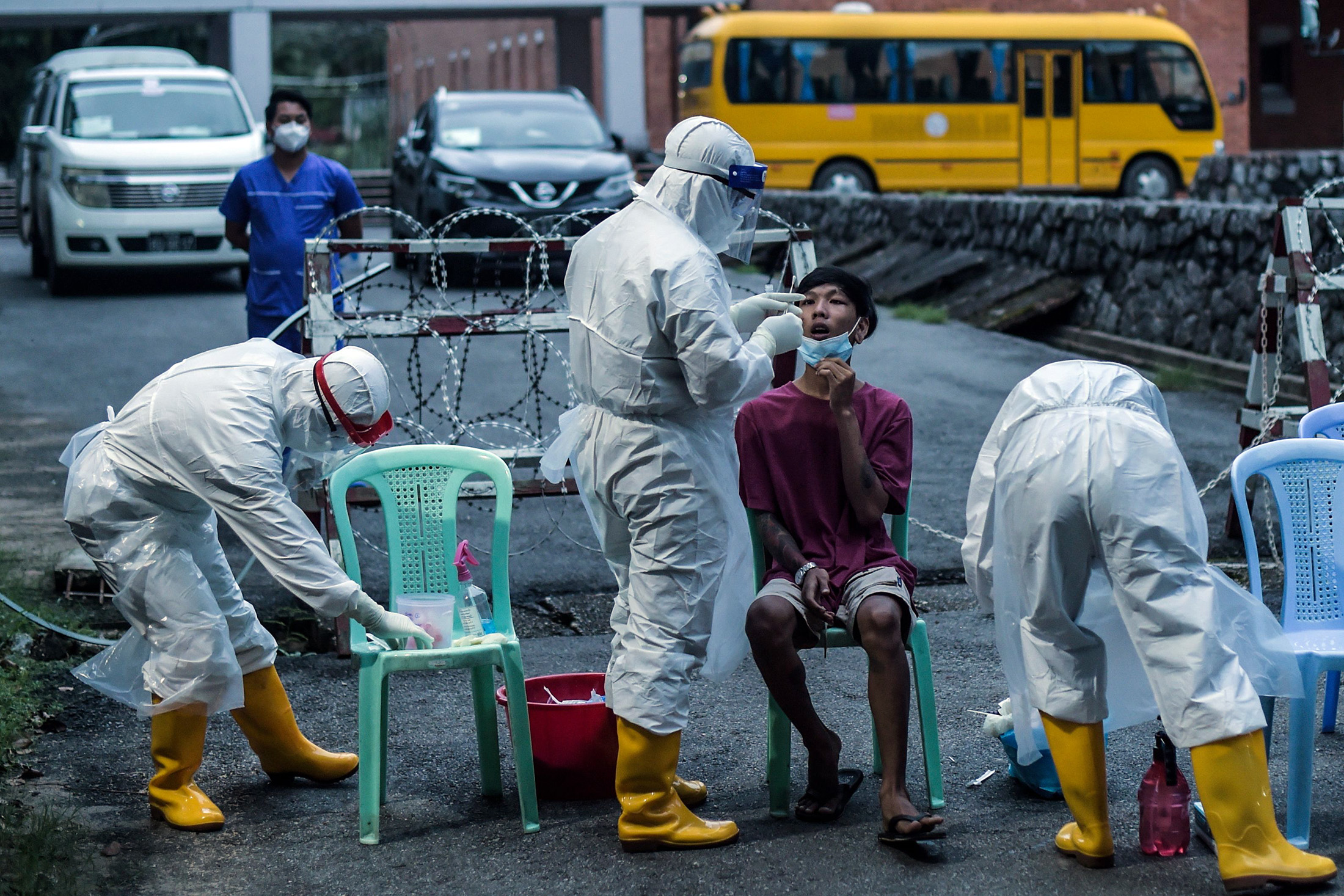 A Health worker collects a swab sample in Yangon on Oct.8.