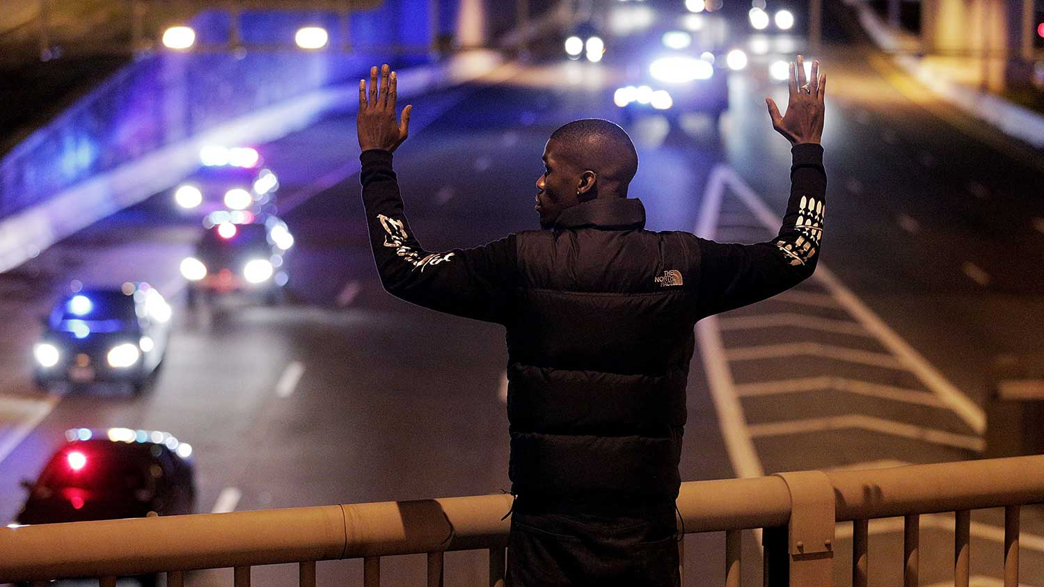 Shaun Reid raises his hands as police follow demonstrators off Highway I-395 during a protest following the grand jury's decision on Dec. 3, 2014, in Washington, D.C.