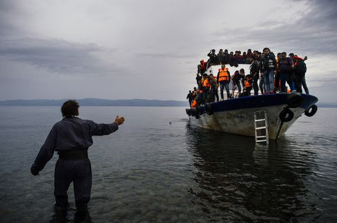 A Greek man greets migrants as they arrive on Lesbos