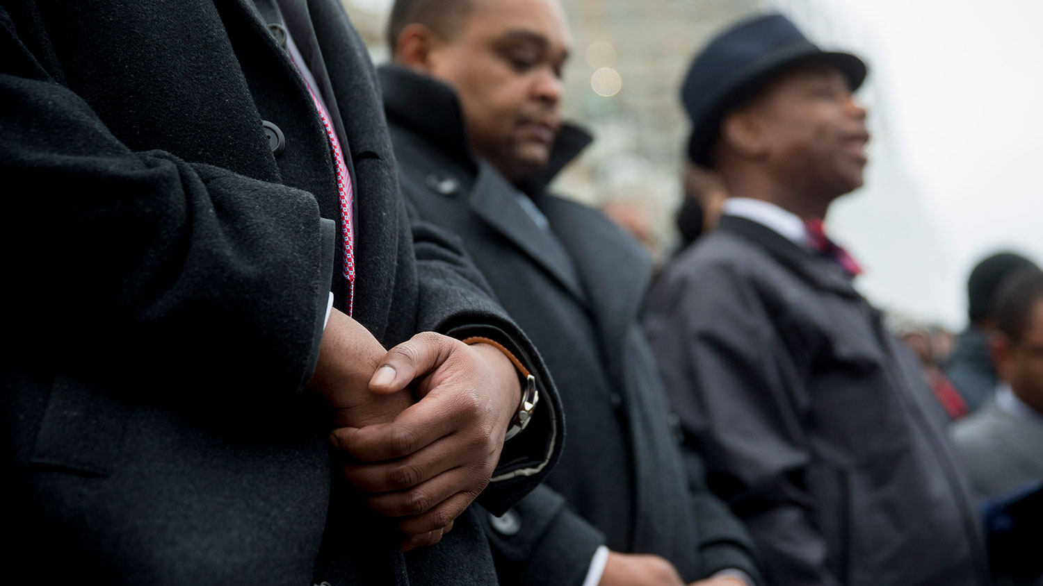 Congressional staff members hold their hands while listening to a prayer by Senate Chaplain Dr. Barry Black, right, during a protest on the U.S. Capitol steps in Washington on Dec. 11, 2014.