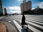 A woman wearing a protective mask crosses a street in Tokyo on January 29, 2020.