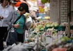 A customer shops for vegetables at a store at the Sunamachi Ginza shopping street in Tokyo.