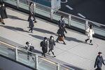 Morning commuters wearing protective masks walk on a footbridge in Tokyo, Japan.
