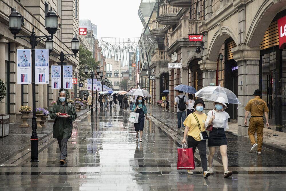 Người đi bộ đi qua các cửa hàng ở Vũ Hán vào ngày 30 tháng 4. Nhiếp ảnh gia: Qilai Shen / Bloomberg